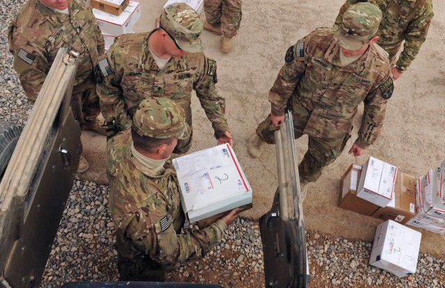 Soldiers and Sailors assigned to Provincial Reconstruction Team  Farah, unload care packages and Christmas gifts during mail call on FOB Farah, Dec. 15, 2019.  Soldiers are reminded to abide by Department of Defense guidelines on receiving gifts during the COVID-19 stay-at-home order.  Gifts distributed at the organizational level could be acceptable gifts under DOD guidelines.