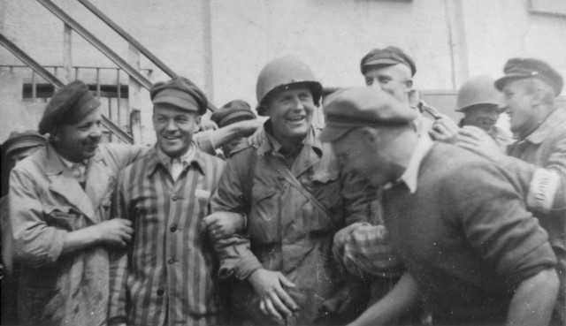 An American Soldier is surrounded by survivors at the newly liberated Dachau concentration camp, April 29, 1945 in Dachau, Germany. American Soldiers of the U.S. 7th Army, including members of the 42nd Infantry and 45th Infantry and 20th Armored Divisions participated in the camp's liberation. U.S. Army photo courtesy of the U.S. Holocaust Memorial Museum.