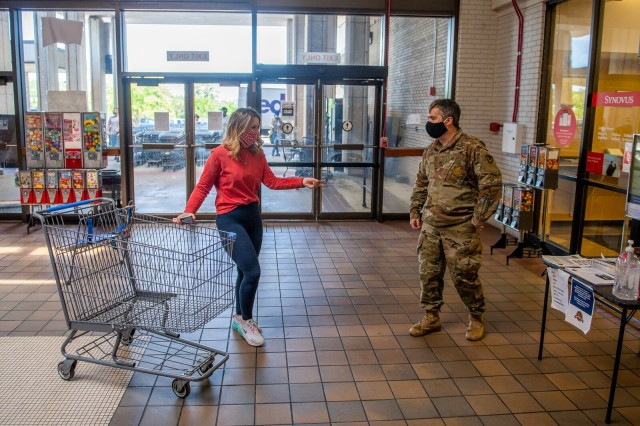 FORT BENNING, Ga. – A Soldier assigned to courtesy patrol duty at the Fort Benning commissary April 15 checks would-be shoppers for proper identification cards and for whether they are they are wearing face masks or similar face coverings, a recent requirement at Department of Defense facilities as a precaution against the spread of COVID-19. Other precautions in place here include a ban on visits for social, recreational and entertainment purposes, but officials are also granting certain requests for visits they deem appropriate.