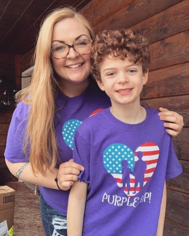"""U.S. Army Garrison Alaska, Fort Greely Child Development Center employee Ms. Joann Amarone poses with her nephew Kieran Amarone for """"Purple Up Day,"""" a virtual celebration of military families worldwide during the Month of the Military Child. Since April 1986, the Army has observed MOMC to recognize and honor the commitment, contributions and sacrifices military children make to our nation through the strength they provide our Soldiers and families."""