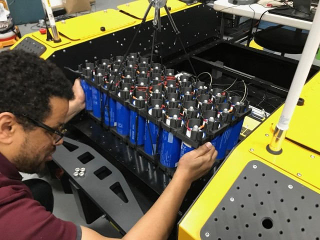 Army electrical engineer Wosen Wolde installs the 2.5 kilowatt-hour lithium battery system designed by CCDC Army Research Laboratory. The battery fills one-third of the vehicle's internal volume.