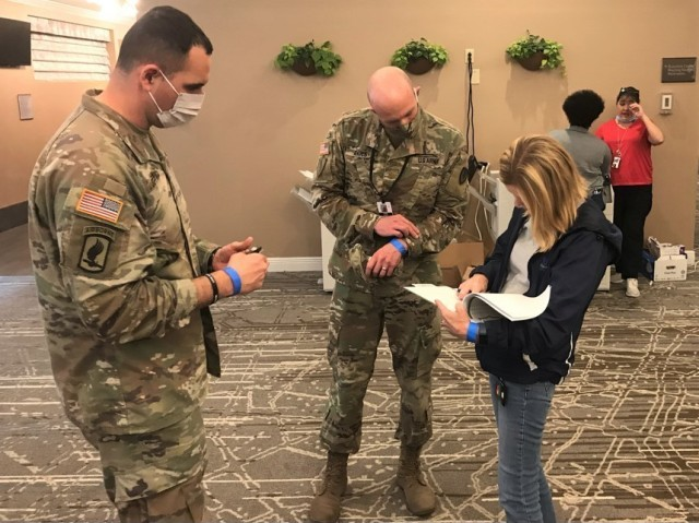 From left, Maj. Charlie Jones and Maj. Jerry Andes check in to COVID-19 Response Center after having their temperatures checked April 10 at the Ernest N. Morial Convention Center in New Orleans. Jones is the 377th Theater Sustainment Command Operational Contract Support Integration Cell officer in charge. Andes is the lead contract support officer at the convention center and is the 904th Contracting Battalion operations officer at Fort Stewart, Georgia.