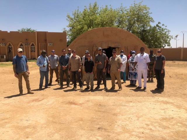 The U.S. Army 443rd Civil Affairs Battalion, Civil Affairs Team 219 and U.S. Air Force civil engineers assigned to Nigerien Air Base 201 near Agadez, Niger, pose for a photo with doctors and nurses from Agadez Regional Public Hospital in front of the tent donated and delivered to the hospital April 6, 2020. CAT 219 reached out to local medical facilities to ascertain what supplies and equipment were needed to assist Nigerien health care providers in protecting themselves and enhancing capabilities to prevent infections and provide effective health care for potential COVID-19 patients. The hospital director requested a tent to be used as a quarantine space in the case of a potential coronavirus outbreak. (U.S. Army photo)