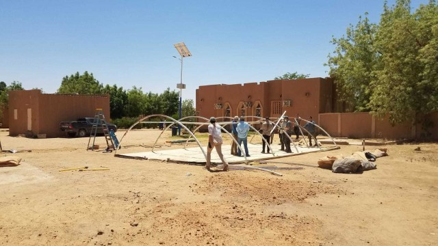 The U.S. Army 443rd Civil Affairs Battalion, Civil Affairs Team 219 and U.S. Air Force civil engineers assigned to Nigerien Air Base 201 in Agadez, Niger, build a tent they donated and delivered to the Agadez Regional Public Hospital April 6, 2020. CAT 219 reached out to local medical facilities to ascertain what supplies and equipment were needed to assist Nigerien health care providers in protecting themselves and enhancing capabilities to prevent infections and provide effective health care for potential COVID-19 patients. The hospital director requested a tent to be used as a quarantine space in the case of a potential coronavirus outbreak. (U.S. Army photo)