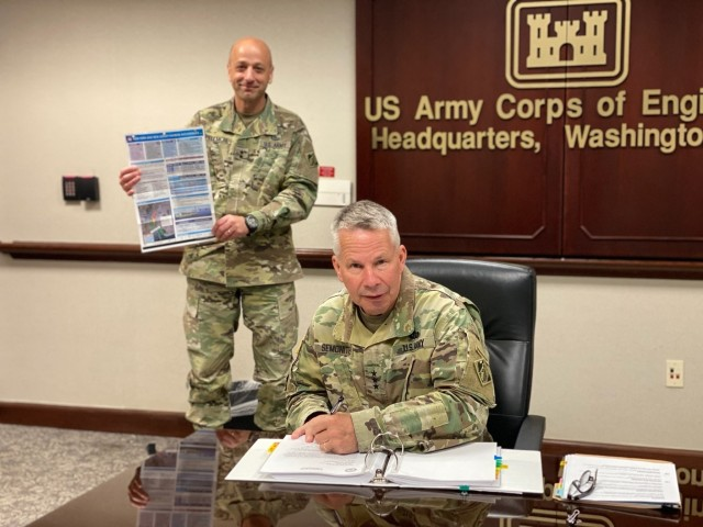 Lt. Gen. Todd Semonite, chief of engineers and U.S. Army Corps of Engineers commanding general, signs a Chief's Report for the New York and New Jersey Harbor Anchorages Study at headquarters in Washington, April 23, 2020. Holding up the study's placemat is Maj. Gen. Scott Spellmon (background), USACE deputy commanding general for civil and emergency operations. The report's signing allows for start of the preconstruction, engineering and design phase. (U.S. Army photo)