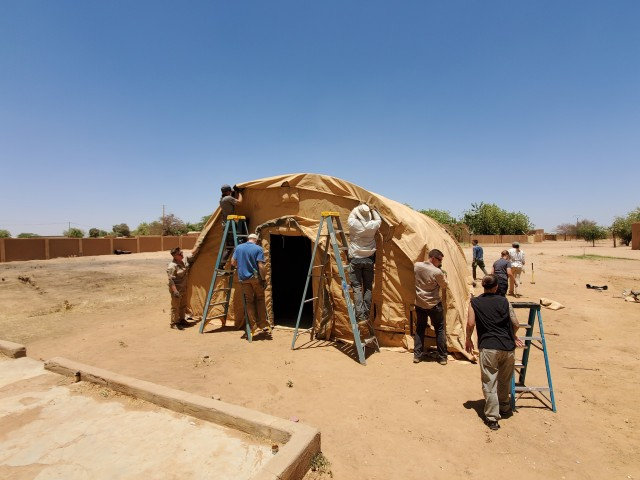 The U.S. Army 443rd Civil Affairs Battalion, Civil Affairs Team 219 and U.S. Air Force civil engineers assigned to Nigerien Air Base 201 in Agadez, Niger, build a tent they donated and delivered to the Agadez Regional Public Hospital April 6, 2020. CAT 219 reached out to local medical facilities to ascertain what supplies and equipment were needed to assist Nigerien health care providers in protecting themselves and enhancing capabilities to prevent infections and provide effective health care for potential COVID-19 patients. The hospital director requested a tent to be used as a quarantine space in the case of a potential coronavirus outbreak (U.S. Army photo)
