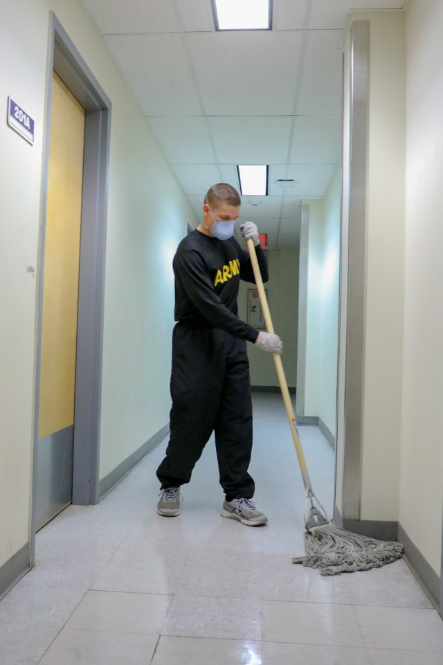 Pvt. Raden Chamber mops the second-floor hall of the quarantine building 3440 on Fort Wainwright as part of the daily routine, 24 April, 2020. The floors and key points are cleaned every three hours with bleach water. (US Army photo provided by Sgt. Christopher B. Dennis)