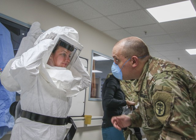 U.S. Army Sgt. Ryan Aker (right), a licensed practical nurse with the Medical-Surgical Unit at Landstuhl Regional Medical Center, assists U.S. Air Force Maj. April Oliver, assistant officer in charge, Intensive Care Unit, LRMC, with donning the Powered Air-Purifying Respirator System to advance COVID-19 patient care and gain experience with donning, doffing and using the PAPR system at LRMC, April 28.