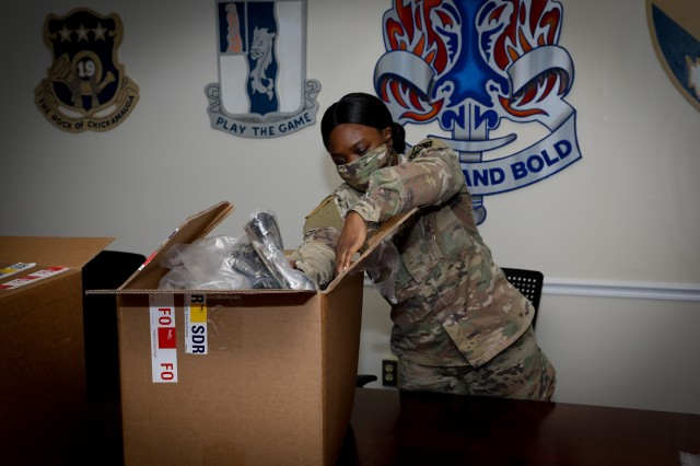 Spc. Rhea Harvey, a supply clerk with the 198th Infantry Brigade, packs a box a cloth face coverings that Combat Capabilities Development Command - Soldier Center in Natick, Massachusetts, made for the Soldiers training at Fort Benning. Nearly 1,500 masks were distributed to 2nd Battalion, 58th Infantry Regiment, April 27.