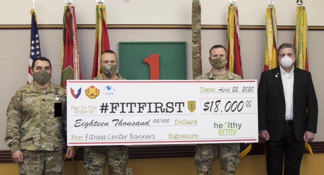 Left to right, Lt. Col. Israel Villarreal, Jr., 1st Infantry Division #FitF1rst coordinator, Command Sgt. Major Raymond Harris, 1st Inf. Div. Command Sgt. Major Timothy Speichert, U.S. Army Garrison Fort Riley and Ken Roynon, Healthy Army Communities Coordinator and Fort Riley Directorate of Family, Morale, Welfare and Recreation Chief, Marketing and Events present a ceremonial check April 22 from U.S. Army Healthy Army Communities program to division leaders.The funds which were secured by DFMWR will be used for fitness center banners and wall wraps.