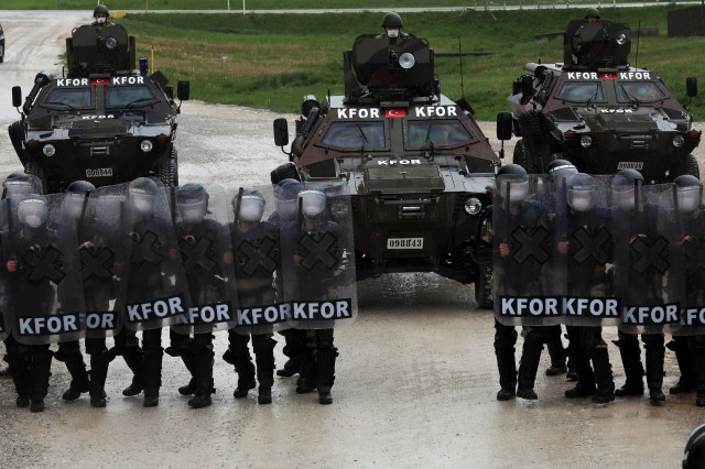 """Turkish Maneuver Company personnel conduct crowd and riot control training May 2, 2020, at Camp Bondsteel, Kosovo.Since 1999, following the adoption of the United Nations Security Council Resolution 1244, the NATO-led Kosovo Force mission has focused on the safety, security and freedom of movement for all the people of Kosovo.In addition to ensuring mission success, KFOR also maintains capabilities in responsive measures to counter deteriorating security situations in Kosovo.The KFOR Regional-Command East's maneuver battalion stands ready throughout Kosovo to respond to crowd and riot control (CRC) situations that may hinder the safety, security or freedom of movement for community members, said U.S. Army Maj. Alex Bear, the maneuver battalion's planning and coordination officer.""""CRC is not the maneuver battalion's primary function. However we are proficient in our CRC capabilities,"""" said Bear. """"We trained for some months before we arrived in Kosovo and regularly rehearse our capabilities here.""""The CRC personnel work together as one with U.S., Turkish and Polish military members, said 1st Lt. Maciej Paszyn, the maneuver battalion's Polish liaison officer.""""It is great to operate alongside our NATO partners and allies,"""" said Paszyn. """"We are stronger together when we bring together our knowledge and capabilities into one effort.""""Capt. Bekir Onur Cetin, the Turkish Maneuver Company's liaison officer, said the Maneuver Company will continue to monitor any potential threats to the safety of Kosovo communities.""""If violence were to ensue during large demonstrations, we must be ready to act,"""" said Cetin. """"We are ready.""""As a well-trained and ready force, the maneuver battalion's CRC personnel remain rapidly deployable throughout KFOR's area of responsibility.In support of the Institutions in Kosovo, the maneuver battalion are a third responder,  the first being the Kosovo Police and the second EULEX, the European Union Rule of the Law.""""Anytime the institutions in Kosovo ask f"""