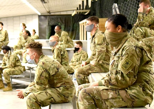 Advanced Individual Training Soldiers listen to a virtual in processing briefing in the US Army Garrison Rheinland-Pfalz Deployment Processing Center. AIT Soldiers on their way to their assignments throughout Germany are being housed by USAG RP for their 14 day quarantine period, as required by the host nation.