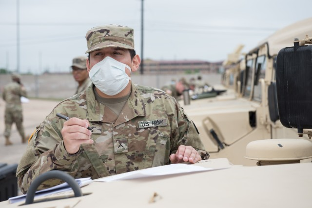 Pv2 Alejandro Robles, Headquarters and Headquarters Company, 13th Expeditionary Sustainment Command, waits for help from one of the mechanics during Maintenance Monday.  Maintaining a high level of readiness during the COVID-19 outbreak is crucial to the success of the Army's mission, and maintenance operations are no fail tasks and can make or break a unit's overall readiness. (U.S. Army photo by Sgt. 1st Class Kelvin Ringold)