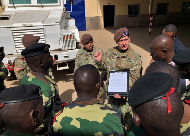 Chief Warrant Officer 3 Yagmur Saylak, center,  assigned to 1st Security Force Assistance Brigade's Logistics Advisor Team 1610 discusses the importance of conducting preventive maintenance with Senegalese soldiers March 3, 2020, in Dakar, Senegal.