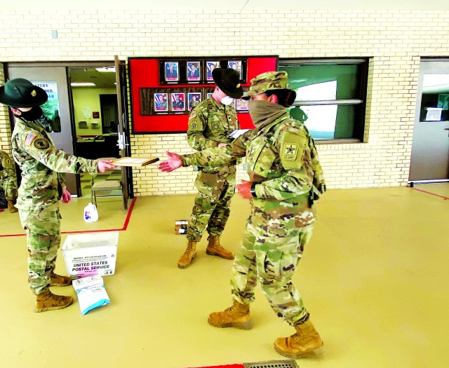 A 1st Battalion, 79th Field Artillery Drill Sergeant, left, hands a piece of mail to a Basic Combat Training Soldier while maintaining social distance and wearing a face mask. Mail call is a welcome connection to loved ones during these stressful times.
