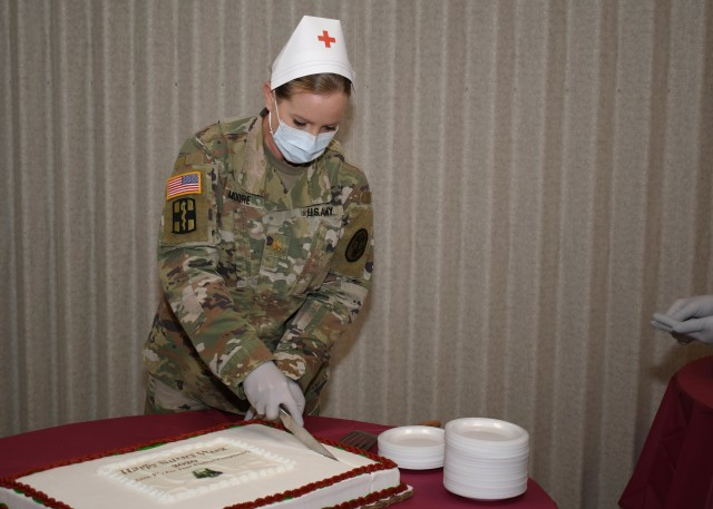 FORT DRUM, N.Y. – Maj. Betty Moore, the chief of ambulatory nursing, U.S. Army Medical Department Activity (MEDDAC), Fort Drum, N.Y., begins cutting a cake during the National Nurses Week kick-off celebration at the Guthrie Ambulatory Healthcare Clinic on Fort Drum, May 6.  (Photo by Warren W. Wright Jr., USA MEDDAC Fort Drum Public Affairs)