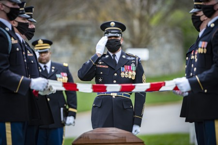 A Soldier assigned to The Old Guard renders honors shortly after the Chaplain provided his blessing during the funeral for U.S. Army Retired Command Sgt. Maj. Robert M. Belch in  National Cemetery, Arlington, Va., April 14, 2020. Given current health protection guidance from the Secretary of Defense, Old Guard Soldiers wear face coverings to mitigate the spread of COVID-19 while executing the Memorial Affairs mission.