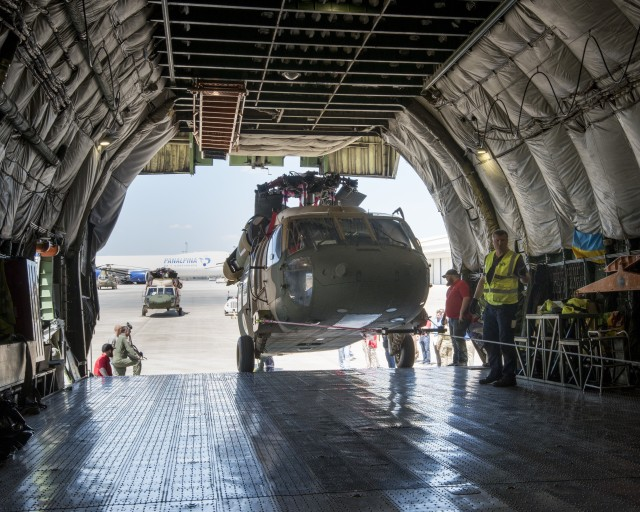 Team members from a Huntsville-based defense industry contractor, SES-I, who refurbished these two UH-60 Black Hawk helicopters for Afghanistan under a U.S Army Security Assistance Command foreign military sales case, upload the helicopters into an Antonov AN-124, at the airfield in Huntsville, AL, 26 April 2019.  US Army photo by Richard Bumgardner, USASAC Public Affairs.