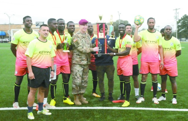 Brig. Gen. Patrick D. Frank, commander, Joint Readiness Training Center and Fort Polk, presents a trophy to members of the Fort Polk soccer team on Anvil Field, the new artificial sports and fitness surface on Fort Polk.
