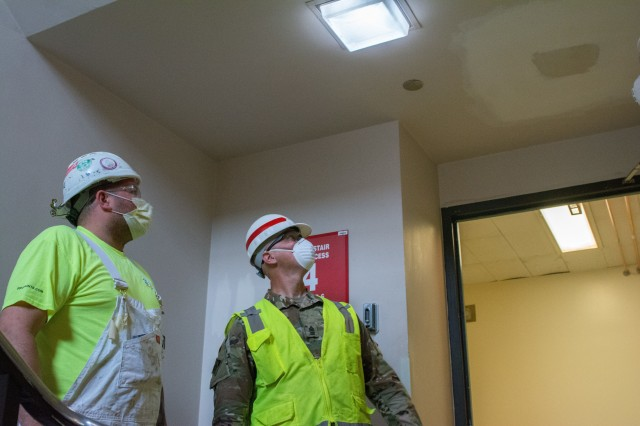 Left, a contract painter provides an update to the progress of his scope of work to Sgt. Maj. John Nelson. Nelson, a U.S. Army Reserve Soldier from the 416th Theater Command supporting U.S. Army Corps of Engineers project to rehabilitate Westlake Hospital in Melrose, Ill. into an alternate care facility (ACF) during the COVID-19 pandemic, April 23, 2020 (U.S. Army photo by Sgt. 1st Class Jason Proseus/416th TEC).