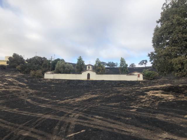 "The Soldier Bowl Amphitheater is Camp Roberts' most unique historic-period property.  It is eligible for listing in the National Register of Historic Places for both its ""Mission Revival"" architectural style, and for its association with USO shows during World War II.  When a wildfire swept through the area in 2019, CA ARNG and CALFire staff rushed to the site, using fire retardant to protect the key built features of the property; note the complete lack of damage to buildings.  The ""bowl"" consists of the natural landform in the background; fire was allowed to burn in these areas in order to eliminate vegetation and avoid the need for mechanical vegetation removal."