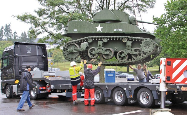 Workers load a World War II M-5A1 Stuart Light Tank onto a truck at the former 1st Armored Division 'Old Ironsides' Museum in Baumholder, Germany on Aug. 21, 2009. The museum moved numerous tanks, half-tracks, artillery pieces and a building full of uniforms, weapons and other military paraphernalia as it followed the division to Fort Bliss, Texas, the new home of the 1AD. (U.S. Army photo)