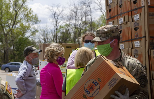 Staff Sgt. Josh Conder, a petroleum supply specialist with Company A, 248th Aviation Support Battalion, Iowa Army National Guard, assists volunteers unloading fresh goods in support of the Hawkeye Area Community Action Program's mobile food pantry outside Lindale Mall in Cedar Rapids, Iowa, on May 6, 2020. With the help of the Soldiers, HACAP was able to help 2,000 people in need of food assistance within the local community. (U.S. Army National Guard photo by Cpl. Samantha Hircock)