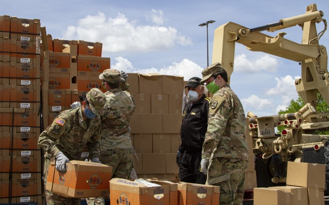 Soldiers with Company A, 248th Aviation Support Battalion, Iowa Army National Guard, assist a volunteer unloading fresh goods in support of the Hawkeye Area Community Action Program's mobile food pantry outside Lindale Mall in Cedar Rapids, Iowa, on May 6, 2020. With the help of the Soldiers, HACAP was able to help 2,000 people in need of food assistance within the local community. (U.S. Army National Guard photo by Cpl. Samantha Hircock)
