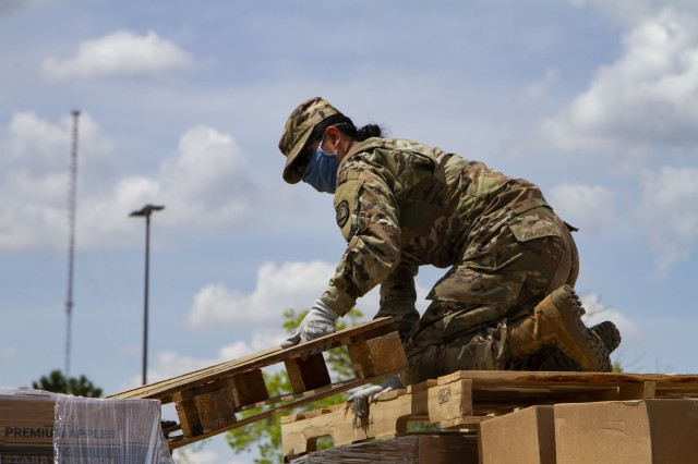 Sgt. Izet Murillo, a petroleum supply specialist with Company A, 248th Aviation Support Battalion, Iowa Army National Guard, unloads pallets of fresh goods in support of the Hawkeye Area Community Action Program's mobile food pantry outside Lindale Mall in Cedar Rapids, Iowa, on May 6, 2020. With the help of the Soldiers, HACAP was able to help 2,000 people in need of food assistance within the local community. (U.S. Army National Guard photo by Cpl. Samantha Hircock)