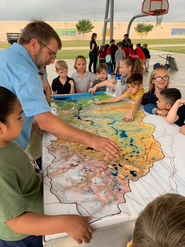 A representative from the Nueces County Storm Water Team shows students how waterways are connected by storm drainage systems.