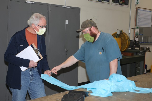 200423-A-BS696-1127 CHAMBERSBURG, Pa. Logan Robinson, Letterkenny Army Depot (LEAD) (right), demonstrates an isolation gown prototype to James Eichelberger, WellSpan, at the LEAD upholstery shop on April 23, 2020. LEAD is currently producing personal protective equipment (PPE) for WellSpan to help combat COVID-19. (U.S. Army photo by Pam Goodhart)