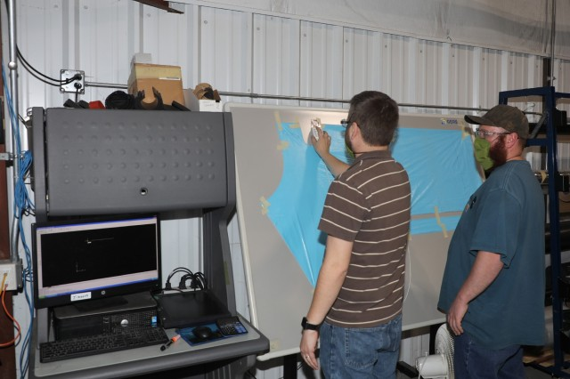 200423-A-BS696-1136 CHAMBERSBURG, Pa. Shawn Hind, Letterkenny Army Depot (LEAD) (left), and Logan Robinson, LEAD, input data into a Computer Numerical Control (CNC) fabric cutter to produce an isolation gown at the LEAD upholstery shop on April 23, 2020. LEAD is currently producing personal protective equipment (PPE) for WellSpan to help combat COVID-19. (U.S. Army photo by Pam Goodhart)