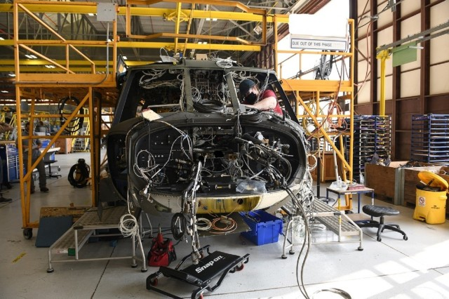 Mary King, aircraft electrician in the avionics/electrical branch at the Corpus Christi Army Depot, Texas, installs the instrument panel wiring harness as part of the assembly and repair of the UH-60L to UH-60V upgrade.