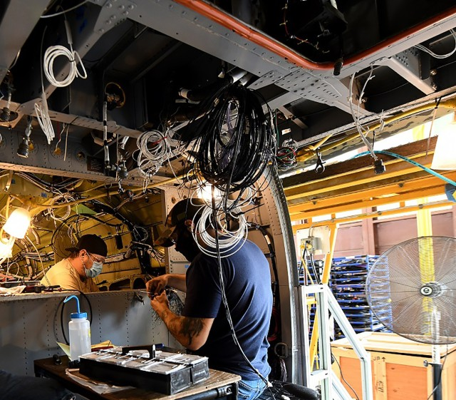 Jonathan Lopez (right) and Michael Lee, aircraft electricians in the assembly repair division at the Corpus Christi Army Depot, Texas, install the data concentrator units wiring as part of the UH-60L to UH-60V helicopter upgrade.