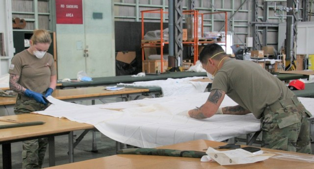 Spc. Kylie Nielsen (left) and Spc. Ernie Ramirez, parachute riggers from the 4th Quartermaster Theater Aerial Delivery Company, measure and cut out templates during the assembly process to produce face masks for U.S. Army Japan. (Photo by Chief Warrant Officer 4 Brian Perinon, Japan Support Team, AFSBn-NEA)