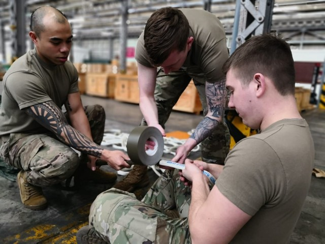 (From left) Sgt. Kenneth Rabina, Spc. Michael McConville and Spc. Keith Shock, 4th Quartermaster Theater Aerial Delivery Company, attach, secure, and tape the centerline to a G-11 parachute apex. (Photo by Chief Warrant Officer 4 Brian Perinon, Japan Support Team, AFSBn-NEA)