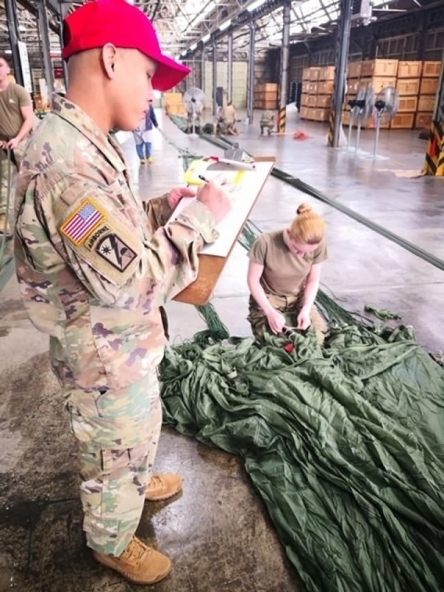 Staff Sgt. Angelito Froa, in-process inspector, observes Spc. Kylie Nielsen as she installs an M-21 reefing line cutter on a G-11 Cargo Parachute System. Both are from the 4th Quartermaster Theater Aerial Delivery Company. (Photo by Chief Warrant Officer 4 Brian Perinon, Japan Support Team, AFSBn-NEA)