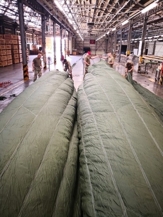 Riggers from the 4th Quartermaster Theater Aerial Delivery Company use an industrial fan to inflate the canopies of a 100 foot diameter G-11 Cargo Parachute System to route the centering lines. (Photo by Chief Warrant Officer 4 Brian Perinon, Japan Support Team, AFSBn-NEA)