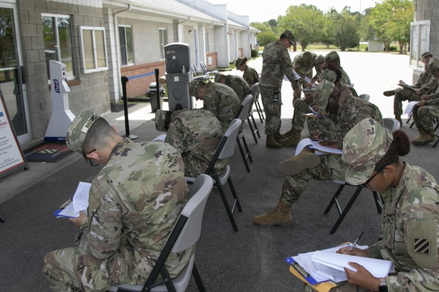 Soldiers arriving by bus from their advanced individual training at Fort Gordon, Ga., fill out initial in-processing paperwork at the Marne Reception Center, Fort Stewart, Ga., May 15, 2020. To maintain the health and safety of incoming personnel and those already stationed at Fort Stewart, COVID-19 temperature screening checks were conducted on these Soldiers before disembarking the bus. (U.S. Army photo by Spc. William Griffen)