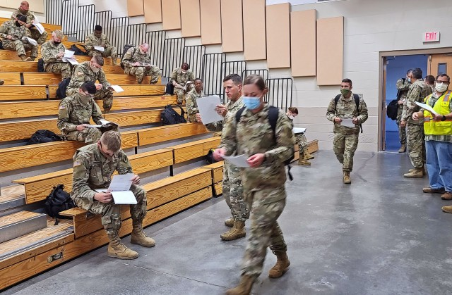 Soldiers fresh out of advanced individual training arriving from Fort Huachuca, Ariz.,fill out their in-processing paperwork at the Truscott Air Terminal at Hunter Army Airfield, Ga., May 13, 2020. To maintain the health and safety of incoming personnel and those already stationed at Fort Stewart and Hunter COVID-19 temperature screening checks were conducted on these Soldiers before disembarking the aircraft. Other precautions implemented include maintaining social distancing, wearing face masks and regular hand washing throughout in-processing procedures. (U.S. Army photo by Sgt. Arjenis Nunez)