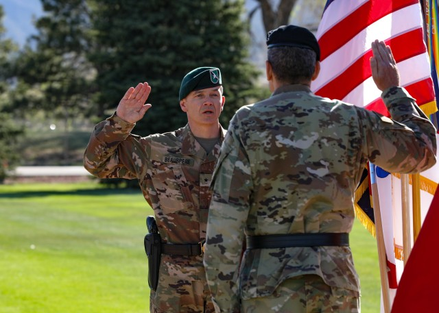 """Maj. Gen. Matthew McFarlane, commanding general of the 4th Inf. Div. and Fort Carson, administer the oath to Brig. Gen. Guillaume """"Will"""" Beaurpere (left), during a promotion and farewell retreat ceremony May 8, 2020, at Manhart Field at Fort Carson, Colorado. McFarlane presented the Legion of Merit to Beaurpere recognizing his exceptionally meritorious service as deputy commander. (U.S. Army photo by Staff Sgt. Inez Hammon)"""