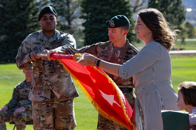 """Brig. Gen. Guillaume """"Will"""" Beaurpere and wife, Amy, unveil the one star flag during his promotion and farewell retreat ceremony May 8, 2020 at Manhart Field at Fort Carson, Colorado. Beaurpere served at the deputy commander of support for the 4th Infantry Division. (U.S. Army photo by Staff Sgt. Inez Hammon)"""