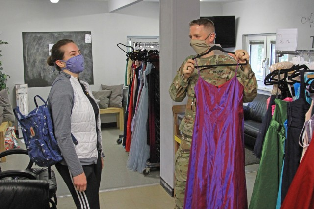 U.S. Army Sgt. Robert Cooper, a crypto linguist with the 24th Military Intelligence Battalion displays a prom dress to Hannah Nuemann, a Wiesbaden High School student during Operation Deploy The Prom on May 16 at the Club Beyond Youth Chapel on U.S. Army Garrison Wiesbaden Hainerberg. Cooper and his wife, Sam Cooper, orchestrated the program Operation Deploy the Prom which gave free ties and dresses to Wiesbaden High School students. (U.S. Army photo by Pfc. Raekwon Jenkins)