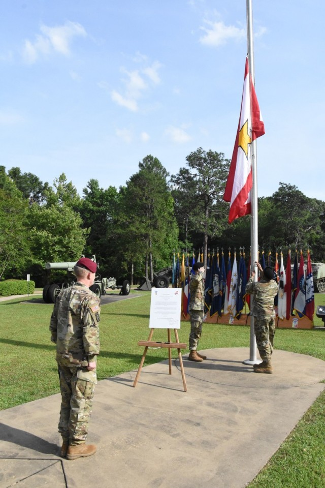 Brig. Gen. Patrick D. Frank, commander, JRTC and Fort Polk, watches as Spc. Joshua D. Cardwell (left) and Sgt. Elvis V. Palarchie, both with Bayne-Jones Army Community Hospital, raise the Gold Star Family Flag at Warrior Memorial Park during a Memorial Day ceremony May 21 at Fort Polk.