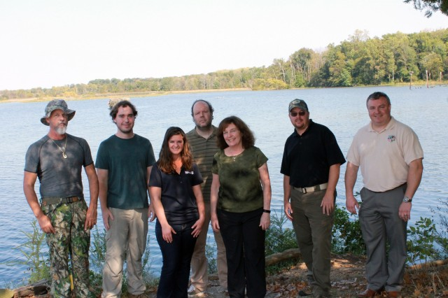 Fort Belvoir Natural Resources Team with Accotink Bay Wildlife Refuge behind.  Fort Belvoir Natural Resources Program Team includes Dorothy Keough, Conservation Branch Chief; Brice Bartley, Urban Forester; Gregory Fleming, Wildlife Biologist; Monica Mundrick, INRMP Implementation Contract Support; John Pilcicki, Threatened and Endangered Species; Andrew Pitt, Wildlife Technician Oak Ridge Institute for Science and Education (ORISE) Program; Kevin Walter, Wildlife Biologist.