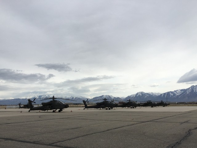 Snow capped mountains of West Jordan, Utah loom behind several AH-64 Apache helicopters as a subtle reminder of the extreme conditions the helicopters and the Soldiers relying on them will encounter.
