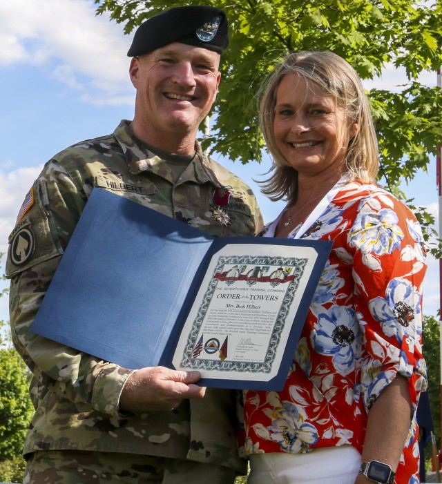 Col. Joseph Hilbert commander, Joint Multinational Readiness Center, poses for a picture with his wife after presenting her with the Order of the Towers certificate during the Service with Honors ceremony in Grafenwoehr, Germany, May 21, 2020. The Service with Honor ceremony, hosted by Brig. Gen. Christopher Norrie, commanding general, 7th Army Training Command, was held to recognize senior leaders for their hard work and dedication while assigned to 7th ATC. (U.S. Army photo by Spc. Zack Stahlberg)