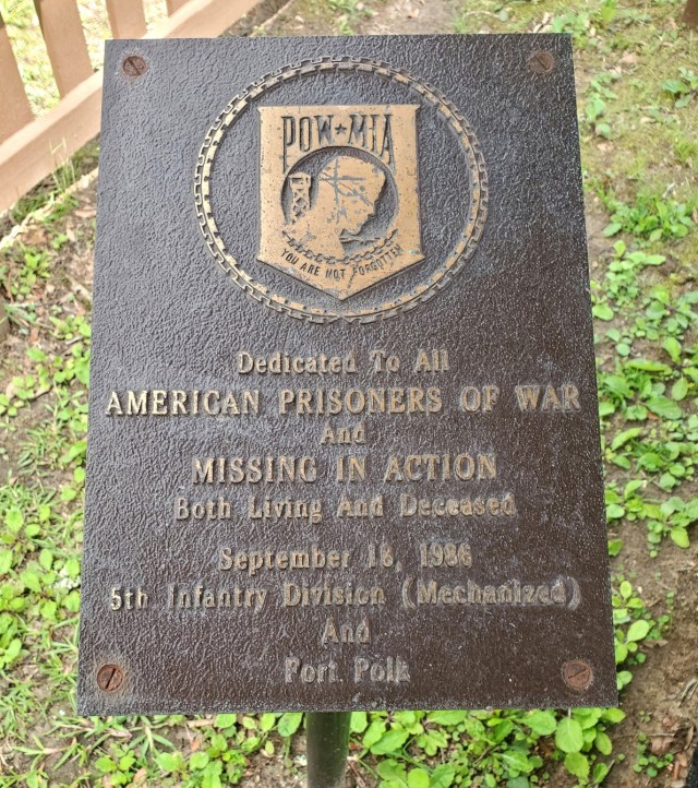 """Pictured is a Prisoner of War/ Missing in Action plaque dedicated to """"All American Prisoners of War and Missing in Action."""" The plaque was dedicated by the 5th Infantry Division and Fort Polk on Sept. 18, 1986; it is located within a gazebo near the Honor Field parking lot."""