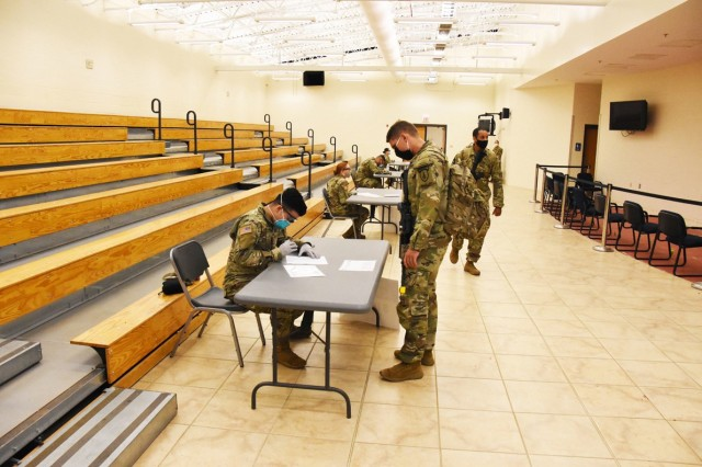 Fort Polk medical personnel process 4th SFAB Soldiers through a medical screening questionnaire station while following social-distancing and face-covering guidelines.