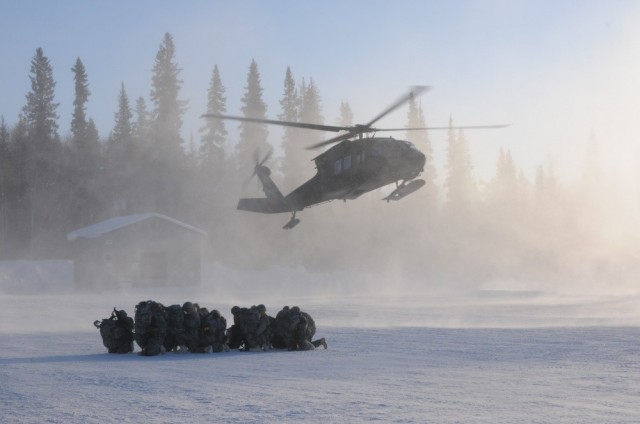 Members of 1st Battalion, 297th Infantry Regiment based in Fairbanks, Alaska and part of the Alaska National Guard, prepare to board a UH-60 Black Hawk Helicopter operated by members of 1st Battalion, 169th Aviation Regiment of the New Hampshire National Guard at Winter Camp Feb.27, on Eielson Air Force Base as part of exercise Arctic Eagle 2020.